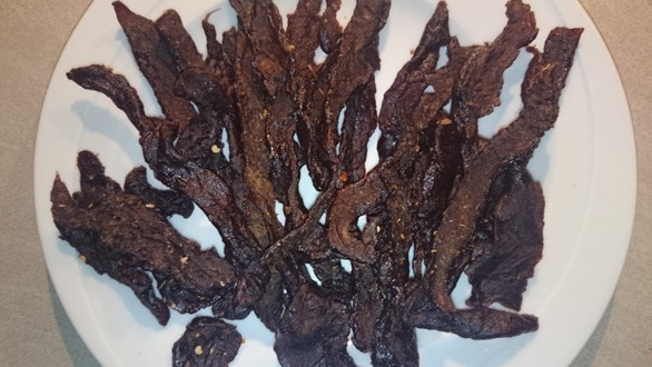 Pictures shows a plate full with a bunch of smoked teriyaki flavored beef jerky