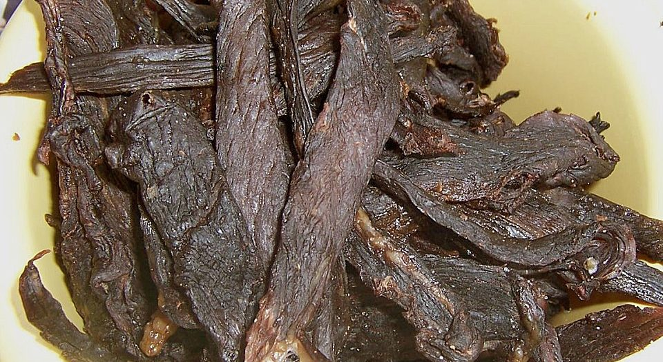 Several stripes of sage jerky in a yellow bowl